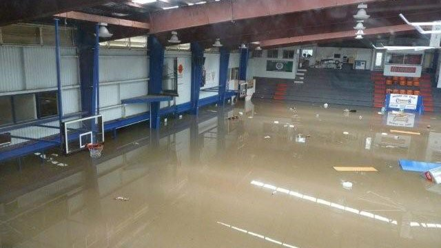The basketball gym where Matt Hodgson and Matt Massey, both members of SUU's basketball team, played in their youth is filled with water from flooding.