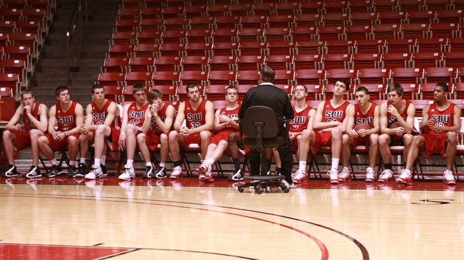 Coach Reid sits with the Mens Basketball team before practice to fine tune there offense and defense for the next game.
