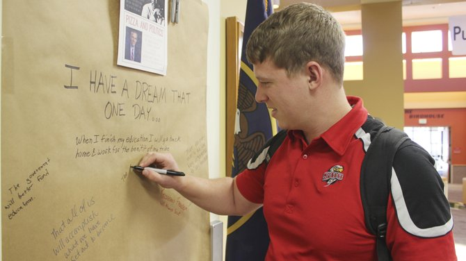 Jeff Hertig, the SUUSA president, signs the Dream Wall. The members of the Michael O. Leavitt Center for Politics & Public Service hosted the event to honor Martin Luther King Jr. day.