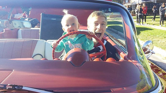 Marshal Beach, a senior interdisciplinary studies major from Orlando, Florida poses with his now 15-month-old daughter Eliza in a car.