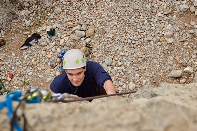 Riley Carter, a freshman chemistry major from West Mountain, reaches for a handhold near the top of his ascent as a part of an SUU Outdoor's rock climbing trip.